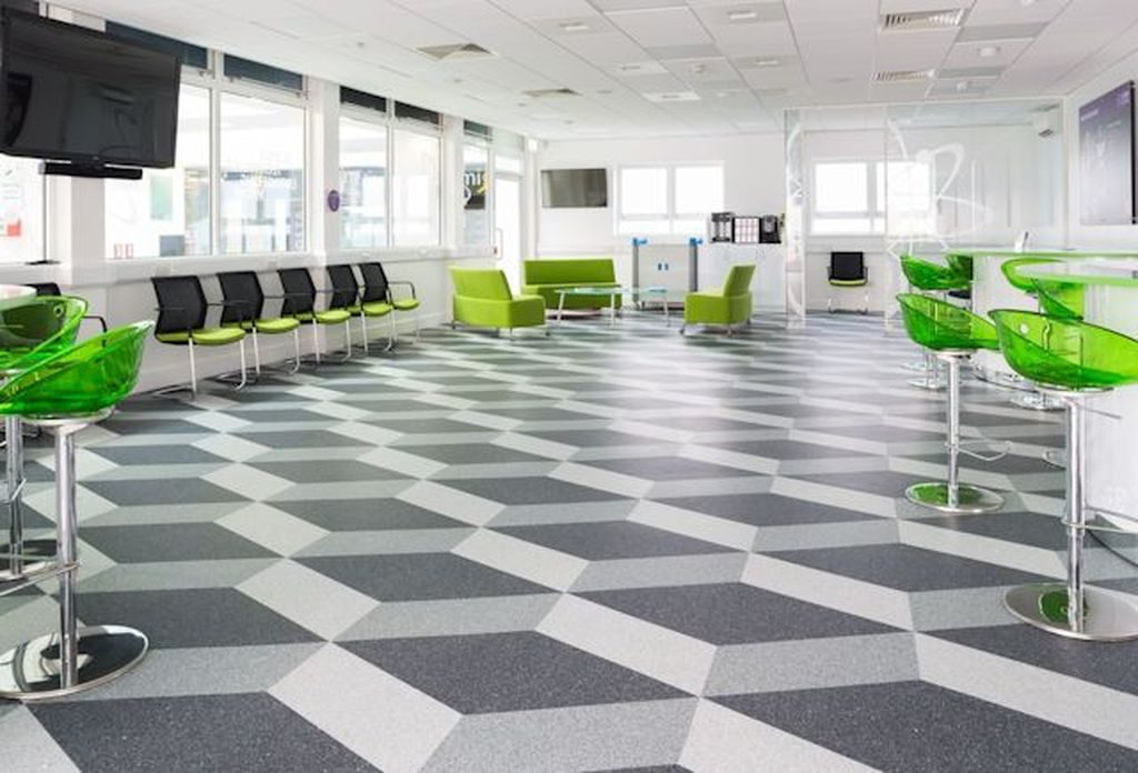 Commercial flooring - an image of a flooring solution that is in a work based canteen are, using a very distinctive and bold design and colours